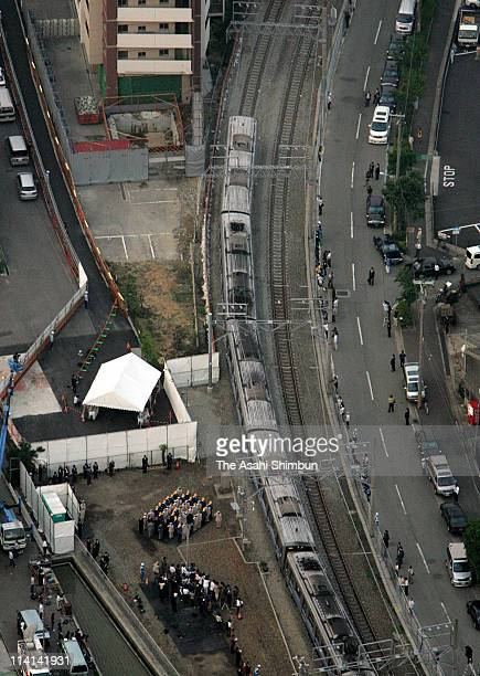 In this aerial image Japan West Railway Co staffs salute as the first Takarazuka Line train runs past the 107 people killed accident site on June 19...