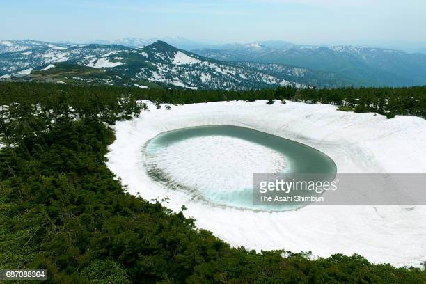 In this aerial image Kagaminuma Pond is seen on May 22 2017 in Hachimantai Iwate Japan Snow melting water creates an eyeshaped pond Hachimantai...
