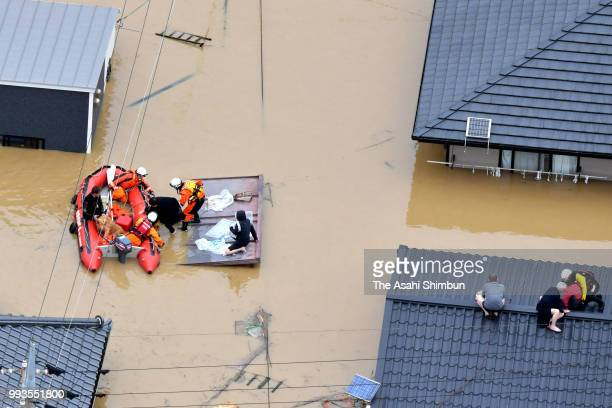 In this aerial image people are rescued from roofs of their houses as the Mabicho area is submerged after Odagawa River banks collapse due to heavy...