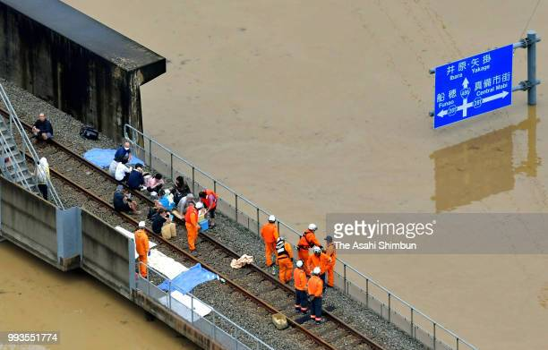 In this aerial image people at a station is rescued as the Mabicho area is submerged after Odagawa River banks collapse due to heavy rain on July 7...