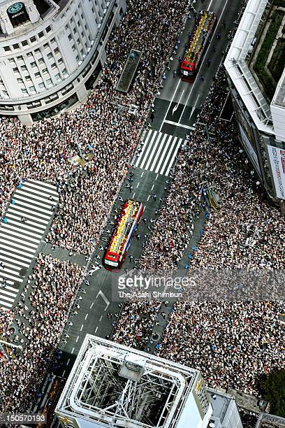In this aerial image people wave hands to Japanfs Olympic medalists as their buses parade on the streets of Tokyoes upmarket Ginza district on...