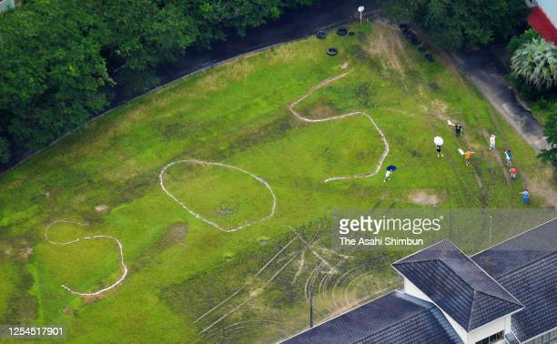 In this aerial image, people wave to the Asahi Shimbun helicopter while letters forming SOS are seen on the grounds of a former elementary school...