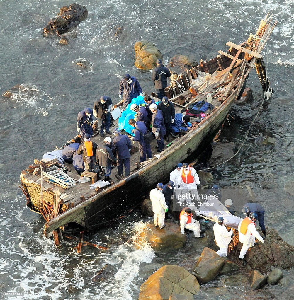 In this aerial image, police officers investigate a wooden boat ashore at a beach on November 28, 2012 in Sado, Niigata, Japan. Five bodies were found in the boat, thought to be the North Korean fishermen escaped from a wrecked fish boat, as some Hangul characters and numbers were marked.