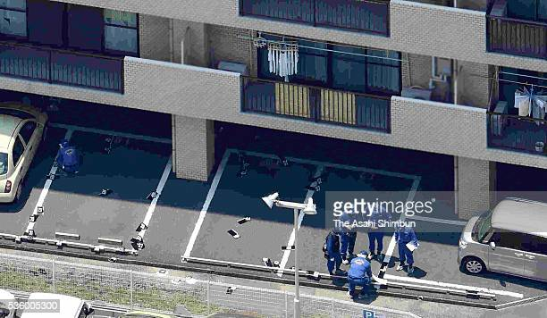 In this aerial image police officers investigate the parking lot of a condominium where Tadashi Takagi was found shot several times in the chest and...