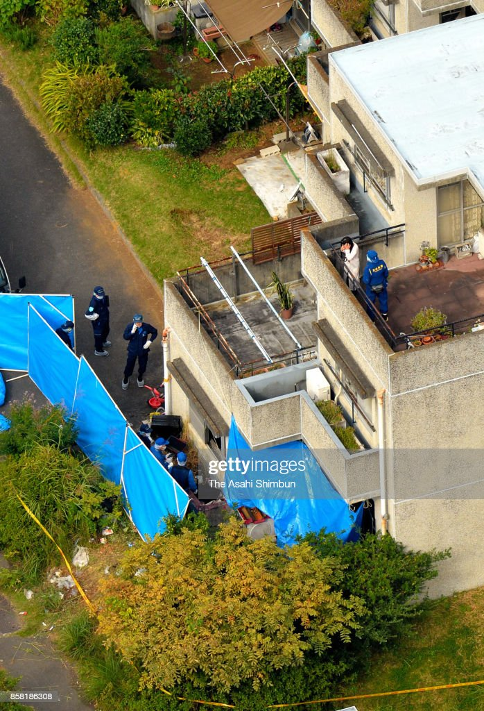 In this aerial image, police officers search the area around the burned-out apartment room in a prefecture-run apartment complex on October 6, 2017 in Hitachi, Ibaraki, Japan. The bodies of a woman and four boys were discovered in a burned-out apartment room after a man told police he had set his home on fire. Hirobumi Komatsu, 32, also told police he had stabbed his family members, investigative sources said. According to police, the six victims are believed to be the suspect's 33-year-old wife; his daughter, 11, an elementary school sixth-grader; his oldest son, 7; second son, 5; and 3-year-old twin sons.