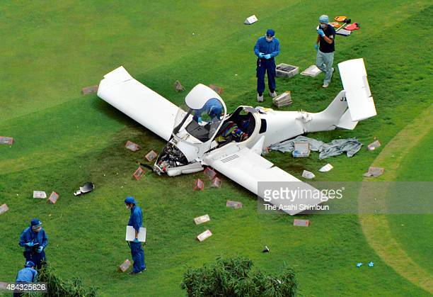 In this aerial image polilce officers investigate an ultra light plane crash at a golf course on August 16 2015 in Tsukuba Ibaraki Japan Two people...