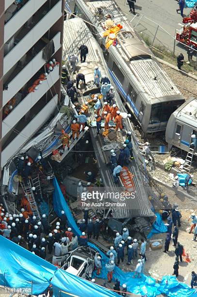 In this aerial image rescue workers attempt to free trapped passengers from a crushed commuter train after it derailed and plunged into an apartment...
