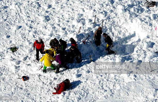 In this aerial image rescue workers dig the snow in searching operation at a snow avalanche site at Mt Masago of the Tateyama Mountains on November...