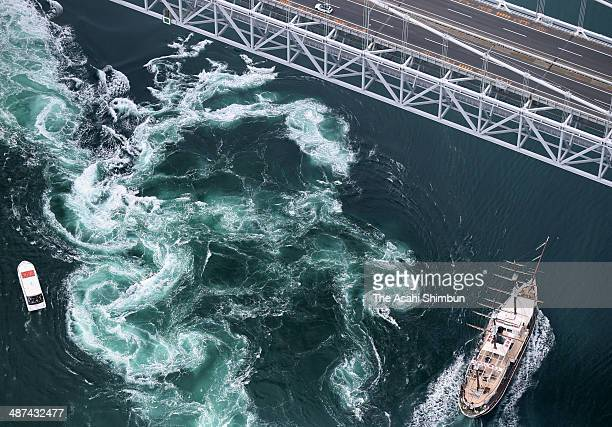 In this aerial image sightseeing boats run around whirling waves at Naruto straits on April 30 2014 in Naruto Tokushima Japan Japan is in the holiday...