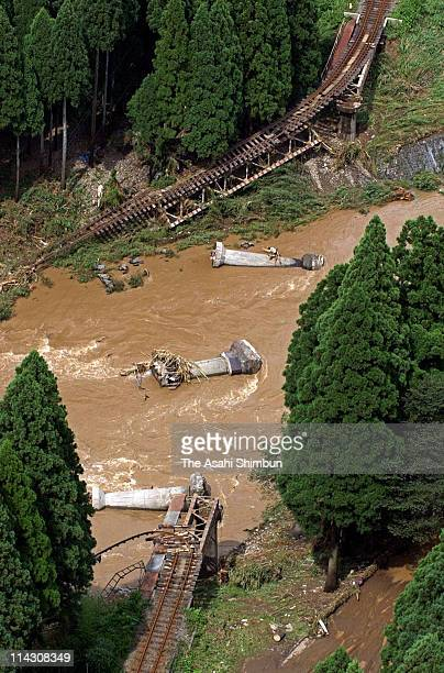 In this aerial image, the bridge of JR Etsumi Hoku Line is washed away by the flooding river on July 19, 2004 in Miyama, Fukui, Japan.