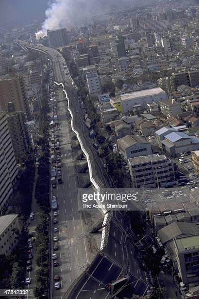 In this aerial image the Hanshin Expressway elevated highway collapses while smoke begins to rise on Janaury 17 1995 in Kobe Hyogo Japan Magnitude 73...
