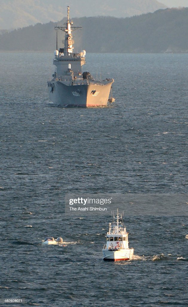 In this aerial image, the overturned boat is being pulled by a Japan Coast Guard ship with the collided vessel 'Osumi' in the background on January 15, 2014 in Otake, Hiroshima, Japan. Two among the four people on the fish boat are reported dead.