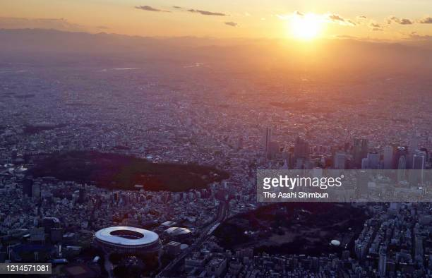 In this aerial image, the sunset is seen over the National Stadium on March 24, 2020 in Tokyo, Japan.