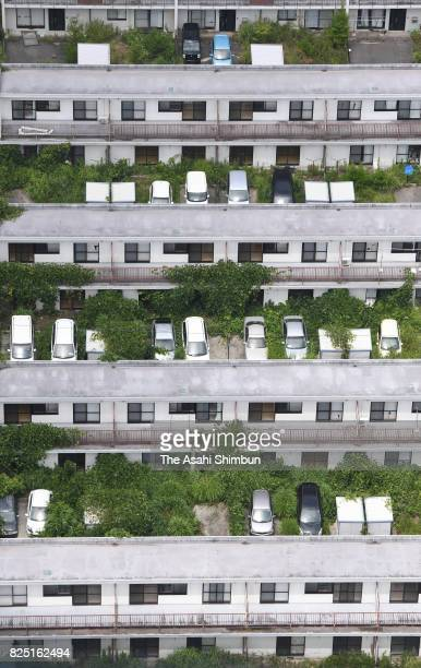 In this aerial image Tokyo Electric Power Co's condominium building is covered with overgrown weeds reaching the second floor inside the...