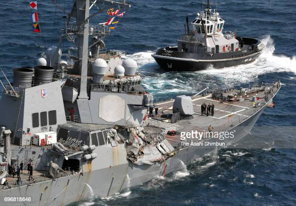 In this aerial image USS Fitzgerald which starboard side is damaged runs with two tugboats toward its Yokosuka Base after collision with the...