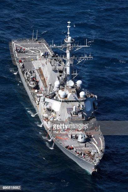In this aerial image USS Fitzgerald which starboard side is damaged runs with tugboats toward its Yokosuka Base after collision with the Philippine...