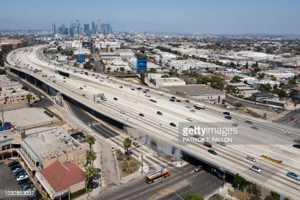 In this aerial image, vehicles drive on the 110 Freeway approaching the downtown Los Angeles skyline on May 12, 2021 in Los Angeles, California.