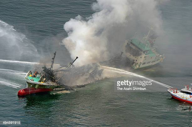 In this aerial image vessels of the Japan Coast Guard discharge water cannon to tanker Shoko Maru on May 29 2014 off Himeji Hyogo Japan The captain...