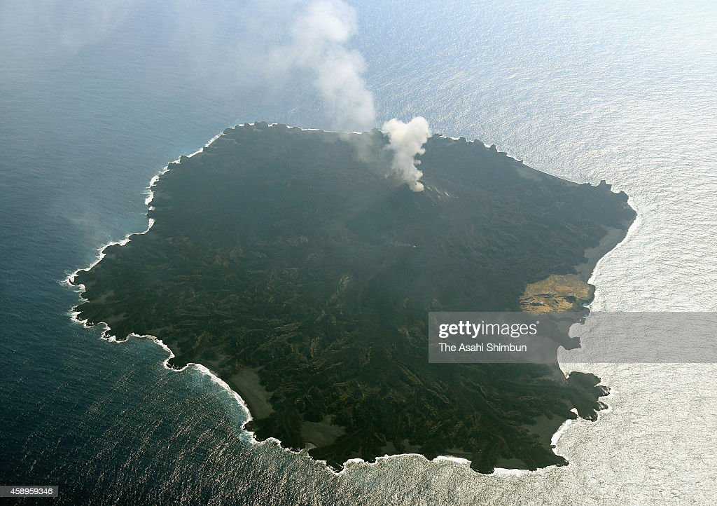 In this aerial image, volcanic eruption continues at the recently formed islet, which is almost swallowing neighboring Nishinoshima island (brown part) on November 13, 2014 in Ogasawara, Tokyo, Japan. The islet was first spotted on November 20, 2013 by the Japan Coast Guard. Lava flows from the continued volcanic activity on the island became connected to nearby Nishinoshima island in late December, the islet has an area of 1.58 square kilometer, 8.6 times bigger than original Noshinoshima island.