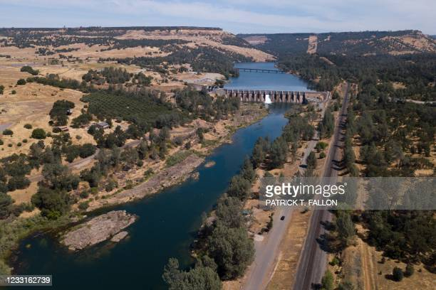 In this aerial image, water flows down the Feather River below the Lake Oroville during the California drought emergency on May 27, 2021 in Oroville,...