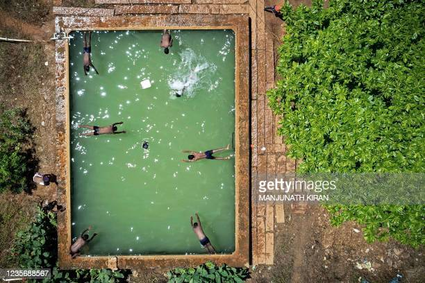 In this aerial photograph taken on October 4 boys dive in an open water tank at a farmland on the outskirts of Bangalore.