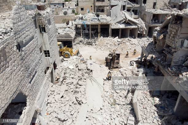 In this aerial picture members of the Syrian civil defence known as the White Helmets use an excavator to search for victims under the rubble...