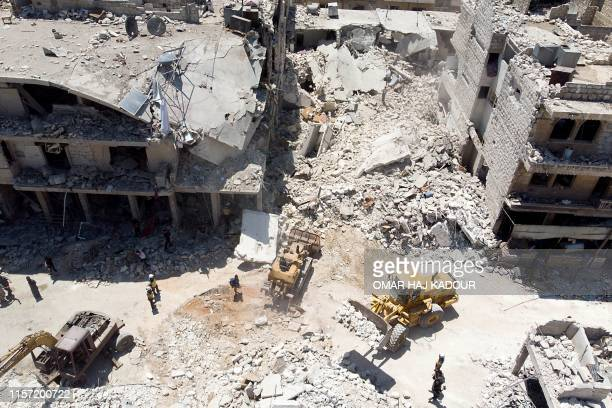 TOPSHOT In this aerial picture members of the Syrian civil defence known as the White Helmets use an excavator to search for victims under the rubble...