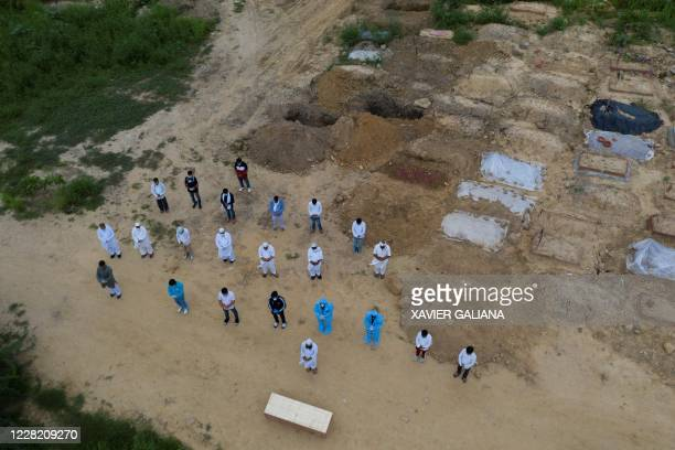 TOPSHOT In this aerial picture relatives volunteers and graveyard workers offer a prayer in front of the coffin of a COVID19 coronavirus victim...