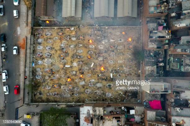 In this aerial picture taken on April 26 burning pyres of victims who lost their lives due to the Covid-19 coronavirus are seen at a cremation ground...
