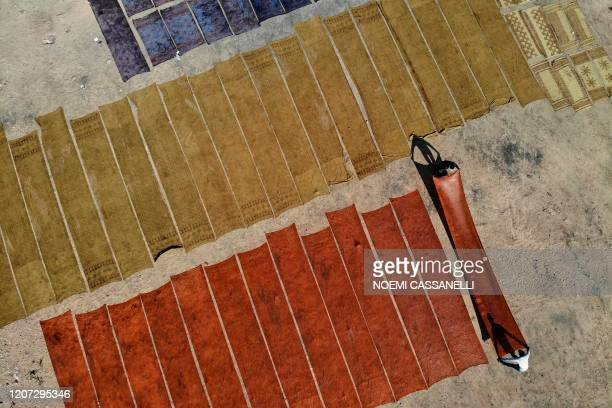 In this aerial picture taken on December 29 artisans lie fabrics on the ground to dry after a synthetic indigo dye process in Bagru village, some 31...