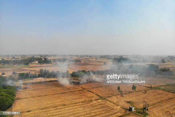 In this aerial picture taken on October 23 smoke rises from the fields as farmers burn straw stubble on the outskirts of Fatehgarh Sahib, in the...