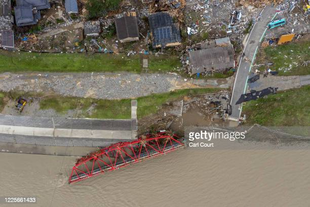 In this aerial view, a destroyed bridge lies in the water next to a ruined village after the Kuma River flooded during torrential rain, on July 8,...