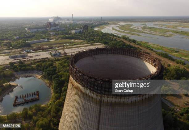 CHORNOBYL' UKRAINE AUGUST 19 In this aerial view a partiallyconstructed and abandoned cooling tower stands as the new enclosure built over stricken...