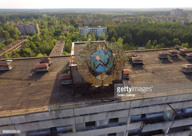 In this aerial view a Sovietera hammer and sickle stands on top of an abandoned apartment building in the ghost town of Pripyat not far from the...