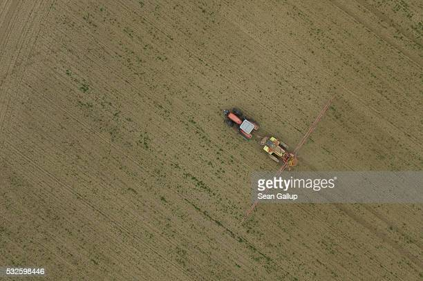 In this aerial view a tractor spreads pesticide on a field on May 19 2016 near Prenzlau Germany Debates among member states of the European Union...