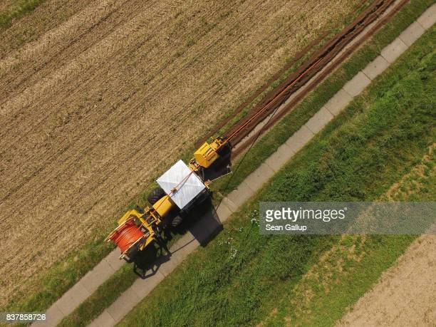 In this aerial view a worker drives a specialzed vehicle that is laying tubing used for running fiber optic cable underground during the installation...