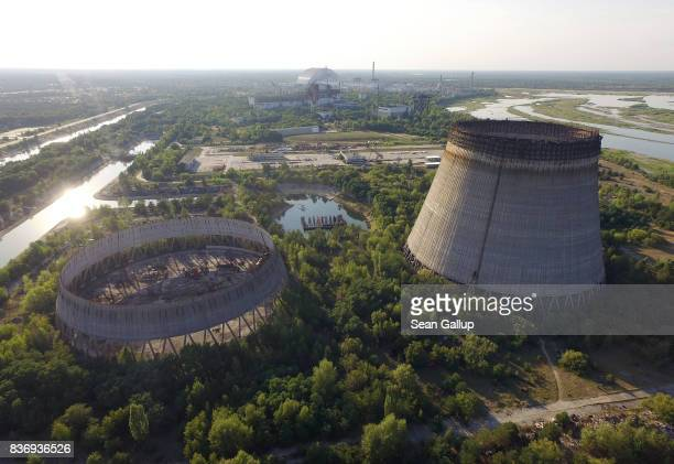 In this aerial view abandoned partiallycompleted cooling towers stand at the Chernobyl nuclear power plant as the new giant enclosure that covers...