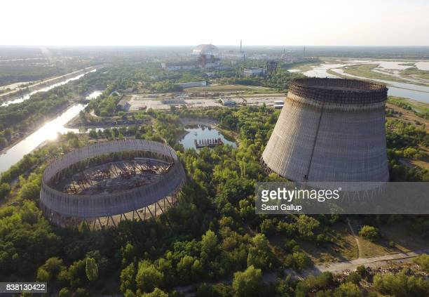 In this aerial view abandoned, partially-completed cooling towers stand at the Chernobyl nuclear power plant as the new, giant enclosure that covers...