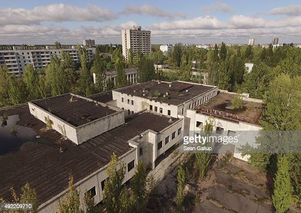 In this aerial view an abandoned restaurant supermarket and apartment buildings stand overgrown with trees on September 30 2015 in Pripyat Ukraine...