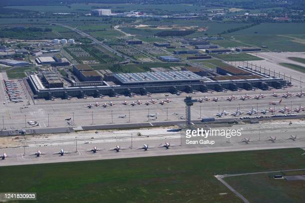 In this aerial view Berlin Brandenburg Airport stands with passenger planes that have been temporarily taken out of service during the coronavirus...