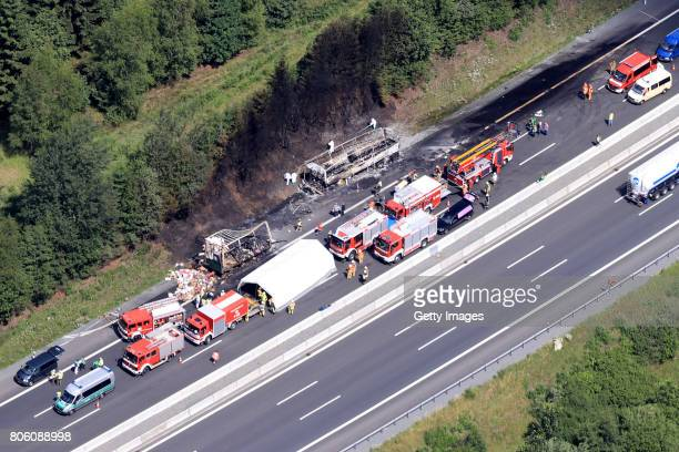 In this aerial view fire and rescue workers stand near the burnedout wreckage of a passenger bus on the A9 highway in northern Bavaria on July 3 2017...
