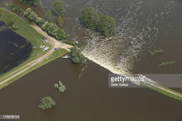 In this aerial view floodwater from the Elbe river flows across a burst dyke to flood land and villages on June 12 2013 at Fischbeck Germany The...