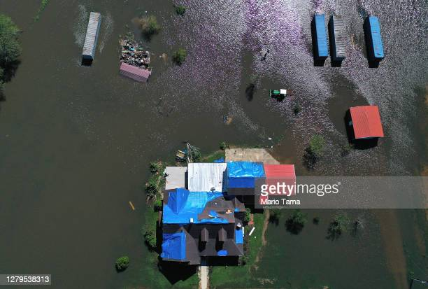 In this aerial view from a drone, a model home is surrounded by flood waters from Hurricane Delta in an area still recovering from Hurricane Laura on...