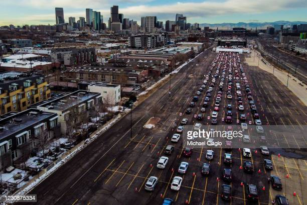 In this aerial view from a drone, cars line up for a mass COVID-19 vaccination event on January 30, 2021 in Denver, Colorado. UCHealth, Colorado's...