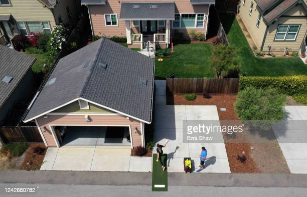 In this aerial view from a drone Olympic softball pitcher Monica Abbott practices by pitching through an open door in a fence to a net in her...