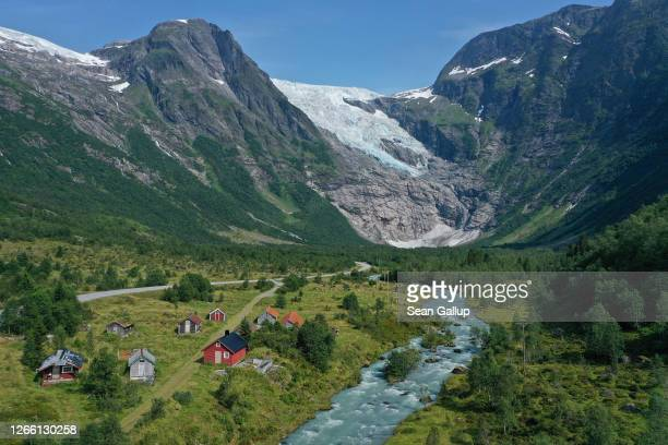 In this aerial view from a drone the Boyabreen glacier lies above rock it ground smooth and once covered deep in ice while meltwater rushes down a...