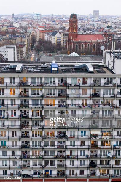 In this aerial view from a drone, the windows of residential apartment buildings stand illuminated towards evening in Schoeneberg district during the...