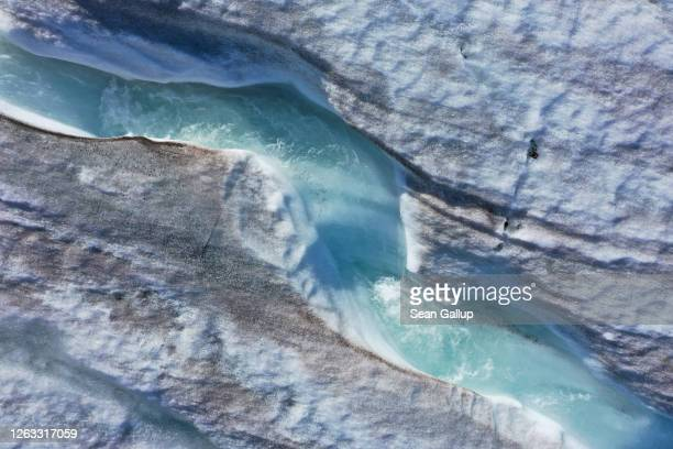 In this aerial view from a drone water carves a winding channel down the surface of the melting Longyearbreen glacier during a summer heat wave on...