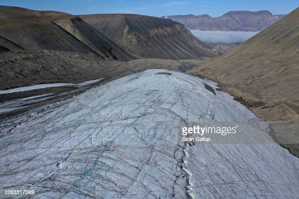 In this aerial view from a drone water carves winding channels down the surface of the melting Longyearbreen glacier during a summer heat wave on...