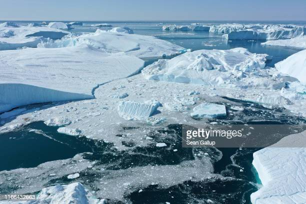 In this aerial view icebergs float at the mouth of the Ilulissat Icefjord during a week of unseasonably warm weather on August 4 2019 near Ilulissat...